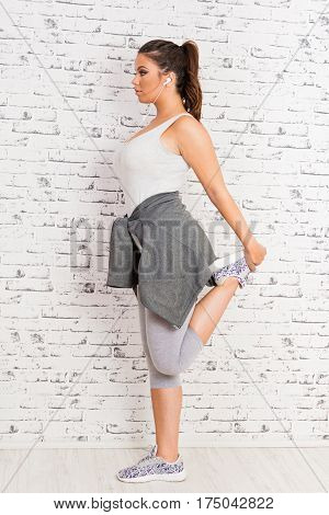 Modern young fitness woman stretching her leg after workout. Beautiful brunette girl in gray sportswear working out at home. Mild retouch, studio lighting.