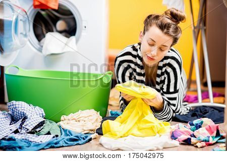 Tired housewife looking on the clothes sitting on the floor near the washing machine at home