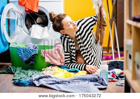 Unhappy housewife holding socks near the washing machine with colorful clothes at home