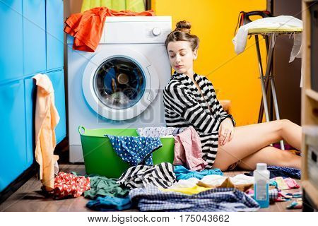 Tired housewife sitting near the washing machine with colorful clothes at home