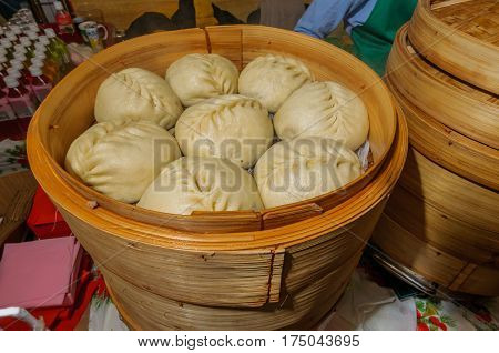 Moscow, Russia - February 25, 2017: National Korean fast food - steamed pies pyan-se in a traditional bamboo steamer