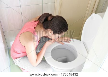 Young vomiting woman near toilet bowl at home