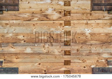 Modern Natural Log Cabin Wall Facade Frame Texture. Rustic Log Wall Square Timber Background. Fragment Of Barn Or House Wall From Unpainted Wooden planks Wallpaper.