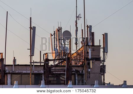 Cellular phone, mobile transmission and telecommunication tower antennas on building roof at sunset, copyspace