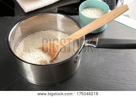 Rice in saucepan on table