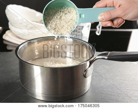 Woman filling saucepan with rice