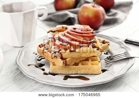 Delicious waffles with apple slices, syrup and sugar powder on plate