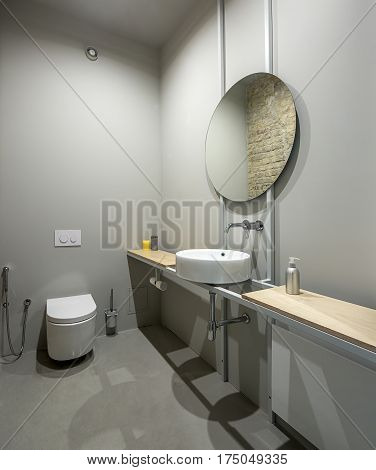Restroom in a loft style with gray walls. There is a white toilet, wooden tabletops with accessories, white sink with a round mirror. Brick wall reflected in the mirror.