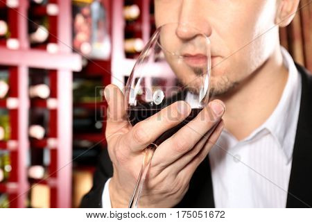 Man with glass of red wine in modern cellar