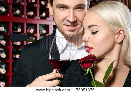 Happy couple drinking in modern wine cellar