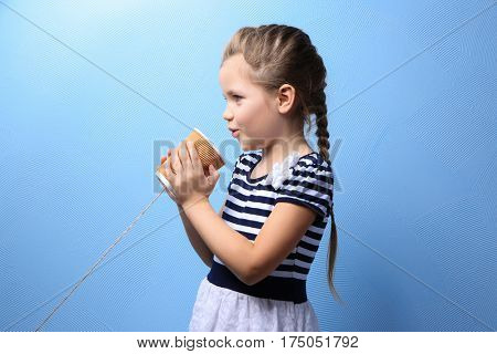 Cute little girl using plastic cup as telephone, on color background