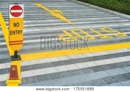 Tiled road with yellow road marking and a No Entry sign. There are dividing lines, guide arrows and a Stop inscription. Closeup. Horizontal.