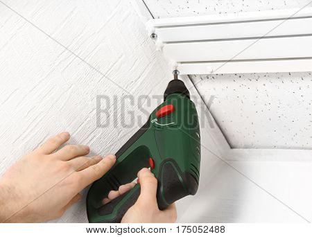 Male hands installing curtain rail using electric screwdriver