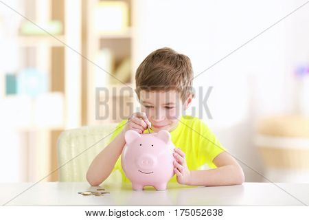Little boy saving coins in piggy bank at home