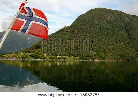 norway flag of a ferryboat sailing in a fjord