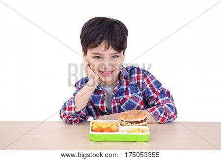 Cute little boy with lunchbox sitting at table, on white background