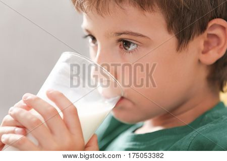Portrait of cute kid drinking milk, closeup