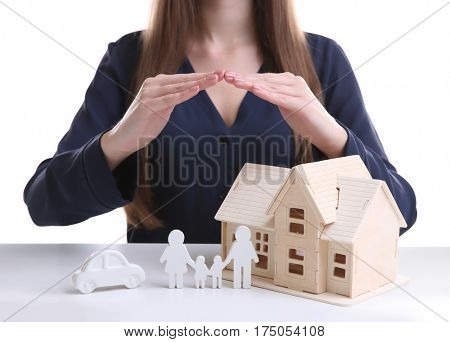 Woman holding hands under model of house, car and family on white table