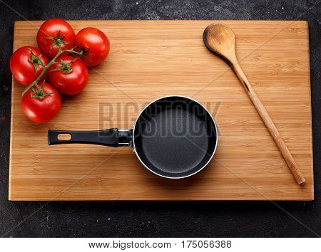 Frying Pan Nd Tomatoe On A Wooden Board