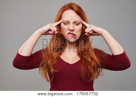 Close-up of confused woman with red hair pressing her forehead with index fingers. Thinking about some plans. Female isolated over gray background