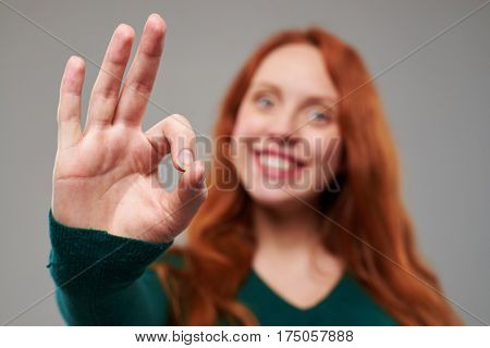 Close-up shot of smiling woman with red hair giving a thumbs up gesture. The concept of success and approval. Focus on hand. Rack focus