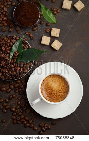 Cup of fresh coffee with coffee beans on dark background, top view