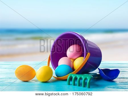 Easter eggs with toddler beach kit on wooden table at shore