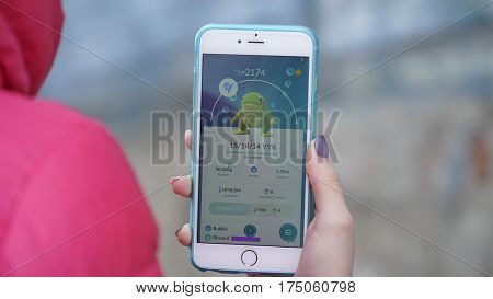 Samara, Russia - March 7, 2017: woman playing pokemon go on his iphone 6s Plus. pokemon go multiplayer game with elements of augmented reality. Politoed was caught. Second generation of Pokemon