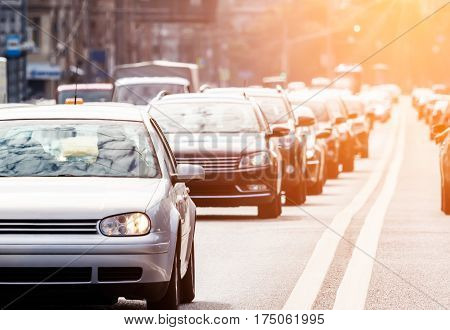 Congested lane with queue of cars against the sun