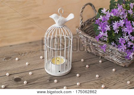 Little light gray wicker basket with beautiful Campanula portenschlagiana. White candlestick in the form of cells with a bird on the surface and scattered beads of pearls.