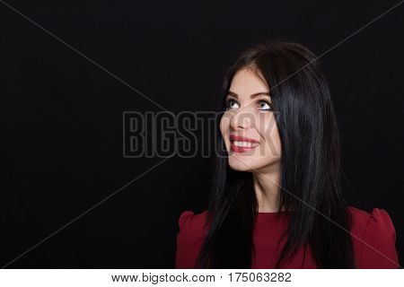 Beautiful woman with black straight hair and blue eyes on a dark background looks away. Close-up. Space for text