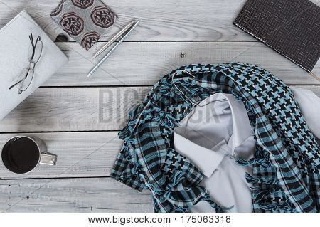 Fragment of a men's shirt with a keffiyeh on a hanger, diary, coffee cup on a wooden painted surface. The pastel colors