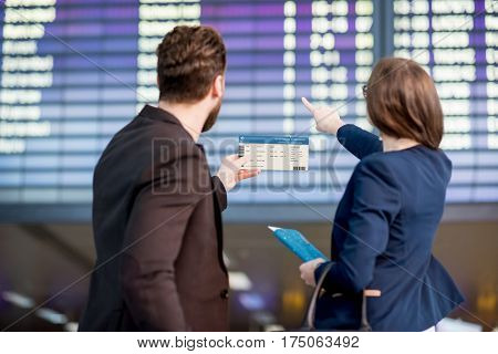 Business couple looking at the timetable holding boarding pass at the airport