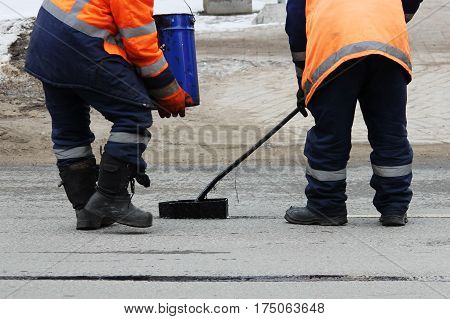Two road workers in overalls are poured with hot tar on the edge of the road strip when repairing the road.