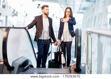 Business couple with baggage checking time getting up on the escalator at the airport