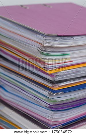 Several multicolored folders with documents stacked in a pile on the table. Close-up