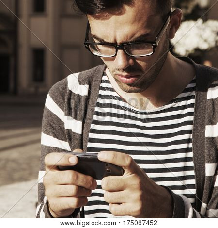 Social Media addiction. young man holding a smartphone(psychological problems media mania)