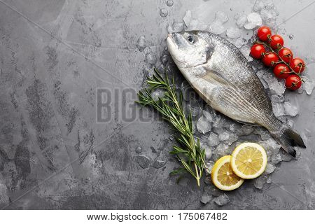 Fresh dorado or gilthead bream cooking with rosemary, cherry tomatoes and lemon on stone background