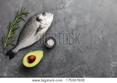 Fresh dorado or gilthead bream cooking with rosemary, avocado, garlic and salt on stone background
