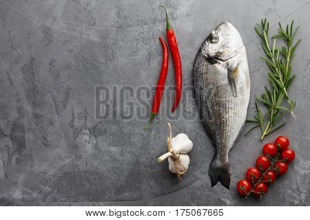 Fresh dorado or gilthead bream cooking with rosemary, cherry tomatoes, chili pepper and garlic on stone background