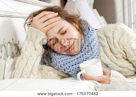 Sick woman with cup of tea. Closeup image of young frustrated sick woman in knitted blue scarf holding a cup of tea while lying in bed. hand on head sad and closed eyes.