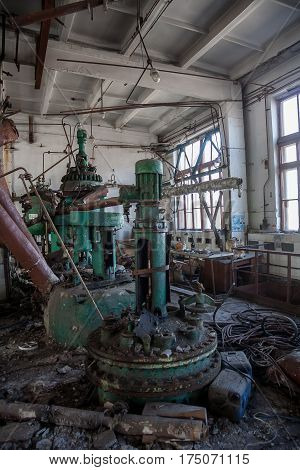 The abandoned chemical pharmacy vitamin plant with the remains of equipment, rusty tanks, tubes and valves