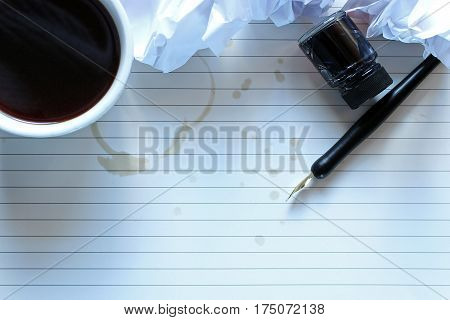 Writer's block desktop with coffee, pen and ink, and wadded up paper mistakes. Open space for copy