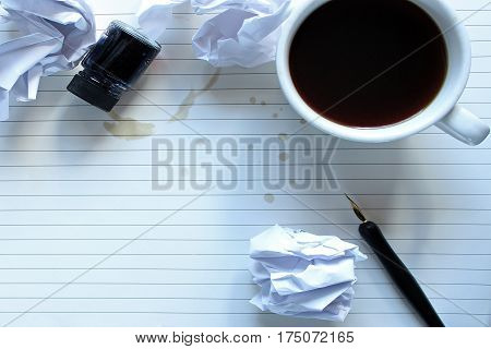 Writer's desktop with wadded up paper mistakes, pen and ink and coffee