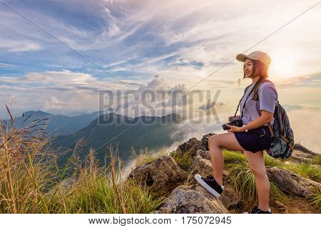 Hiker asian young woman happy with camera backpack and caps looking beautiful landscape nature of mountain and colourful sky at sunset on viewpoint Phu Chi Fa Forest Park Chiang Rai Thailand