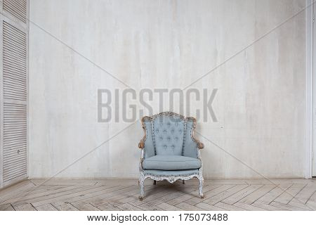 Old antique armchair furniture against light grey grungy wall. Abstract empty room