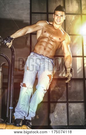 Handsome, muscular young man smiling, shirtless in jeans, hanging from metal handle