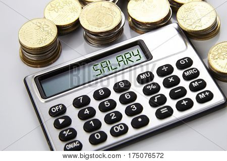 few stacks of coins and calculator with text on screen salary