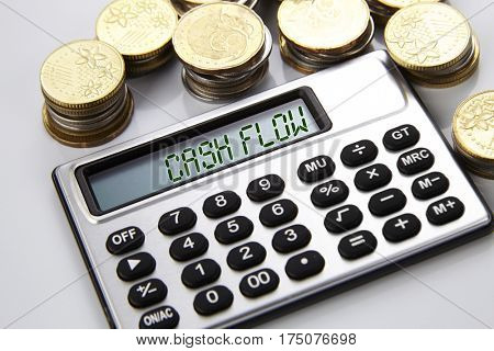 few stacks of coins and calculator with text on screen cash flow