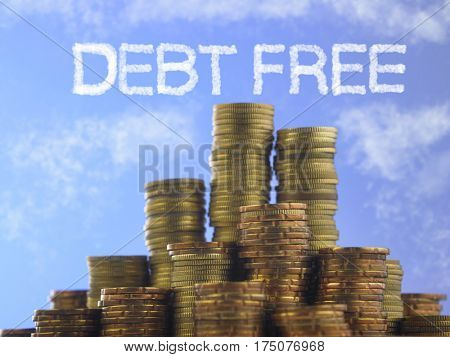 Many piles of coins against  blue sky with text debt free